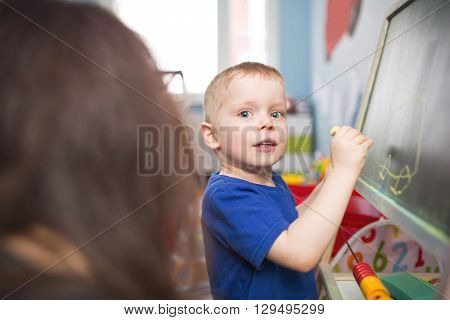 A photo of small boy drawing a car on the blackboard. His mom is looking after him.