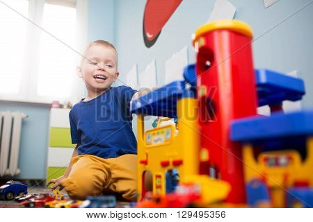 Small Boy Playing With Toy Car Park