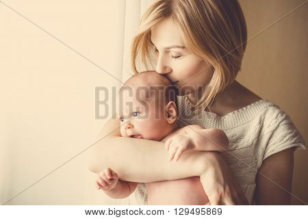 newborn baby in a tender embrace of mother at the window. mother holding a small child in the window