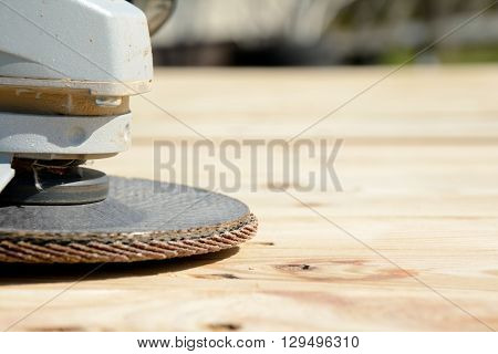 Front part of angle grinder with abrasive disc on planks after work. Shallow depth of field.
