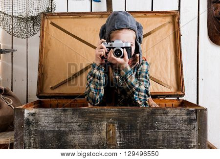 little girl in wooden chest taking ptoto with rarity camera