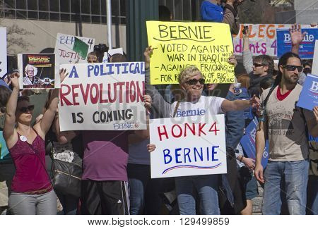 Asheville, North Carolina, USA - February 28, 2016: Crowd of Bernie Sanders supporters enthusiastically stand on a street corner holding signs and interacting with cars and passersby during a political rally on February 28 2016 in downtown Asheville, NC