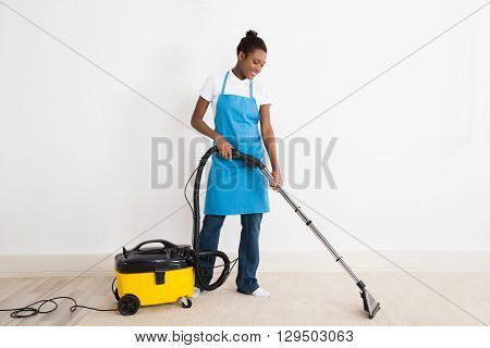 Young Happy Female Janitor Using Vacuum Cleaner On Floor At Office