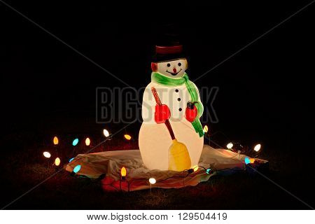 Snowman at night with lights create the spirit for the Holiday.
