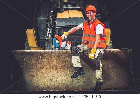 Bulldozer Works Concept. Young Caucasian Men Seating and Relaxing on Bulldozer Blade. Happy Construction Worker. Ground Works.