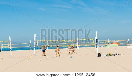 Hermosa Beach, California, USA - October 8, 2015; Women tanned and fit playing Beach volleyball under Californian summer sky on Hermosa Beach