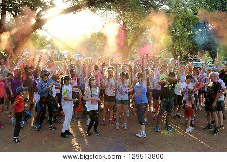 Rustenburg Marathon Club Rainbow Run - NOVEMBER 25: Crowd of runners throwing powder paint into air at start of colour run on November 25 2015 Rustenburg South Africa. poster
