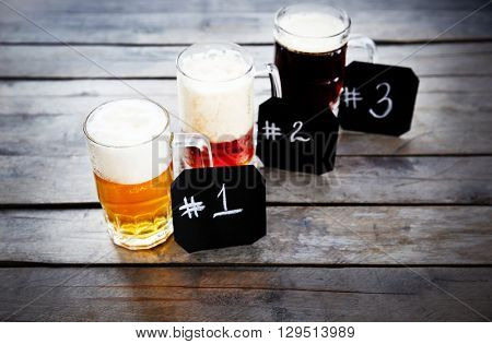 Glasses with different sorts of craft beer and numbering on wooden table. Retro stylization