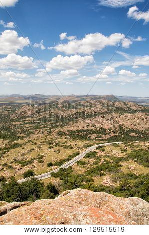 Road winding through an arid landscape between outcrops of rock at Wichita Mountains