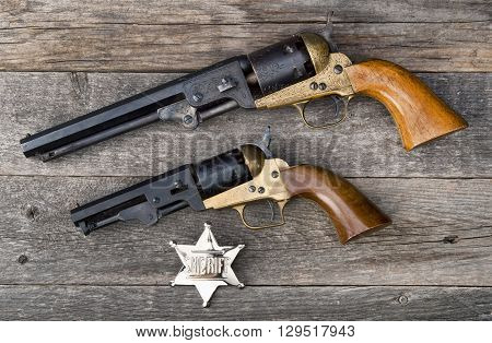 The guns that won the west and silver sheriff badge. poster