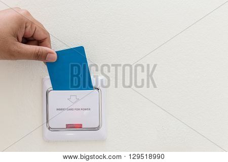 Hand Holding Blue Hotel Key Card Insert To Electric Switch