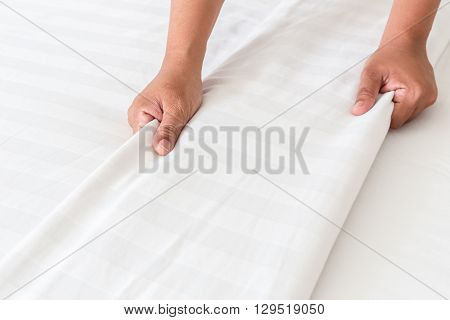 Hand Set Up White Bed Sheet In Hotel Room