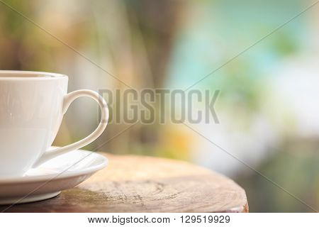 White Coffee Cup On Table In Garden With Blur Light Bokeh