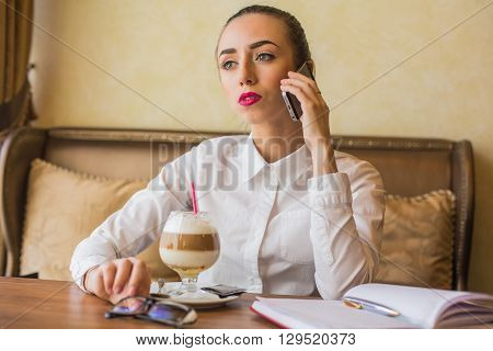 Brunette woman in business clothes sitting at the cafe drinking latte coffee and speaking with her mobile phone.