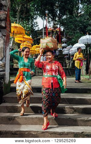 UBUD INDONESIA - MARCH 02: Balinese women in traditional clothes carrying ceremonial box with offerings on the head during Balinese New Year or Nyepi Day celebrations on March 02 2016 in Ubud Bali.