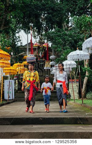 UBUD INDONESIA - MARCH 03: Balinese family in traditional clothes going to the temple during Balinese New Year or Nyepi Day celebrations on March 03 2016 in Ubud Bali.