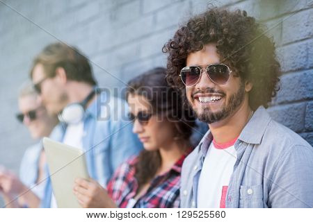 Young man in sunglasses smiling at camera while friends using digital tablet in background