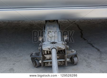 Dusty pneumatic jack under car. The jack with roller photographed in close-up.