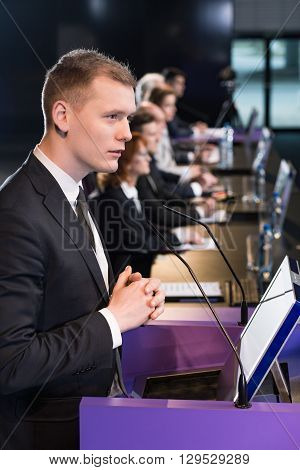 Man in suit standing at lectern with microphone