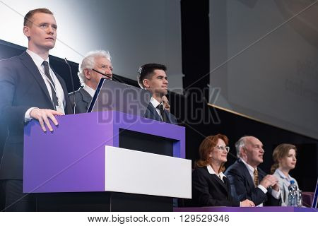 Young businessman standing at podium with corporate colleagues