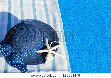 towel and summer blue hat with starfish near water of pool