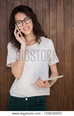 A businesswoman is having a phonecall in a wooden background