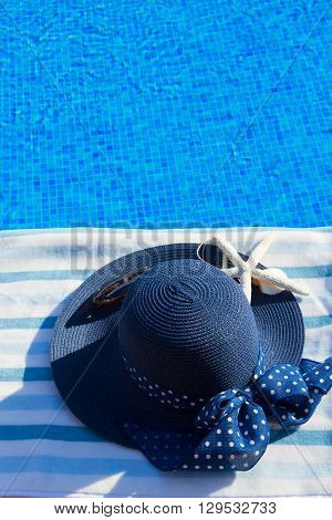 towel and summer blue hat with seashells near pool, copy space on blue water