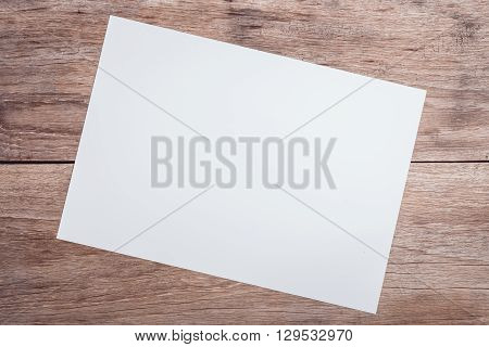 Empty White Paper On Wooden Table Top View