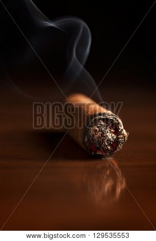 Fuming Havana cigar on a wooden table (with reflection on the table)