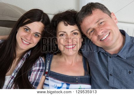 Portrait Of Family  With Their Teenage Daughter At Home