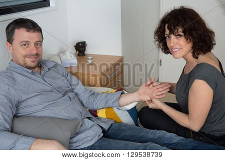 Woman Therapist Reading In The Palm Of Hand Of Male