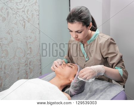Spa therapy for young woman receiving facial mask at beauty salon. Beautician and client before Facial Mask in beauty salon. Beautician worker applying facial cosmetic mask to client in beauty salon.