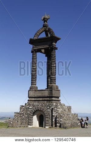 GERGOVIE FRANCE May 5 2016 : Tourists loook at the monument on the Gergovie Plateau dedicated to Vercingetorix designed by Jean Teillard in 1903.