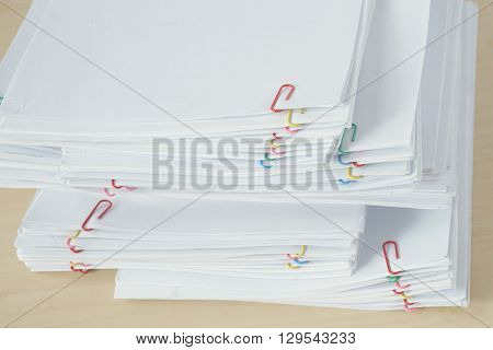 Pile Of Workload Paperwork And Reports With Colorful Paper Clip