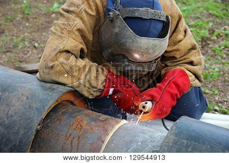 Welder with protective equipment welding outdoors. Selective focus.