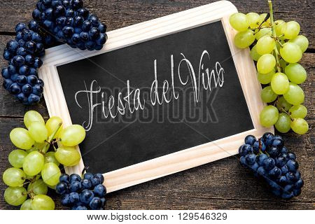 white and blue grapes with a slate on wooden table spanish text fiesta del vino on it which means wine festival