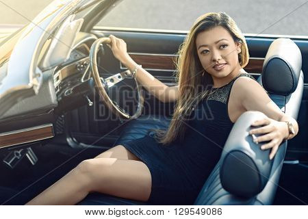 Attractive girl sitting in vintage car parked on the street