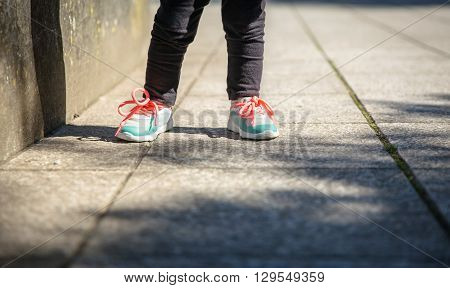 Closeup of little girl legs with sneakers and black leggins training outdoors