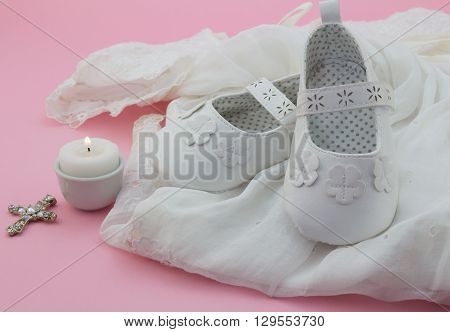 Baby girl shoes cross and candle on white lace with pink background