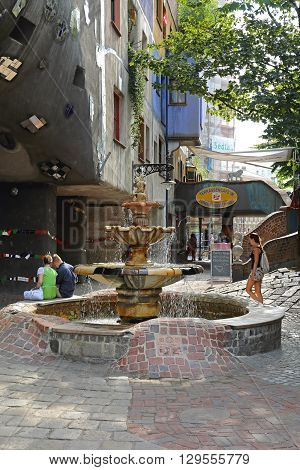 VIENNA AUSTRIA - JULY 12: Hundertwasser Fountain with Tourists in Wien on JULY 12 2015. Tourists around Ceramic Fountain of Architect Hundertwasser in Vienna Austria.