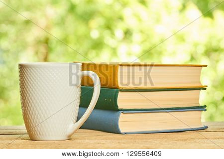 Cup and stack of books on the wooden table on green background