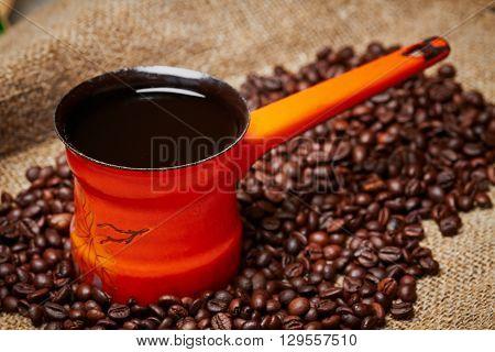 Orange turkish coffee pot on grains and sackcloth