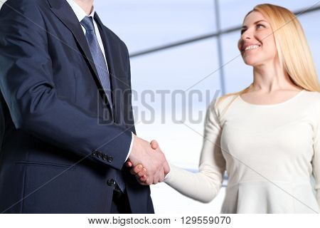 The Close-up image of a firm handshake between two colleagues in office. poster
