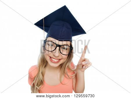 people, graduation and education concept - smiling young student woman in mortarboard and eyeglasses pointing finger up