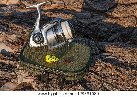 Fishing reel on the natural background. Fishing bait with small red silicone worm. Objects on the green box for fishing bait on the old tree with brown bark.