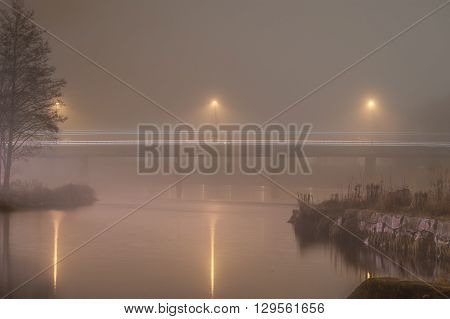 Bridge over water in thick november fog. Long exposure time shows lines from traffic.
