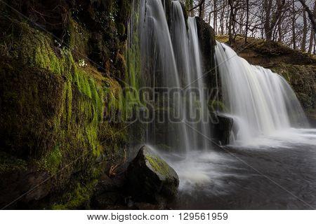 Moss covered Sgwd Ddwli Uchaf waterfalls on the river Neath, near Pontneddfechan in South Wales, UK