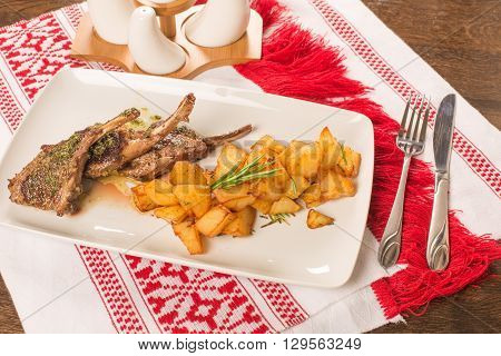 Grilled lamb chops on a white plate, in a rustic arrangement