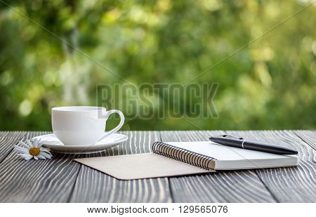 blank white notebook pen and cup of coffee on the desk
