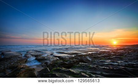 a stacked image of a stunning sunset over the rocky beach. capturing the movement of the water and the contrasting colours in the sky.